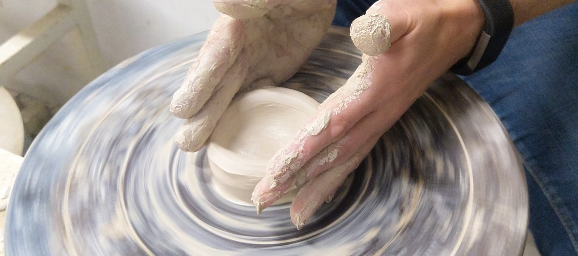 two hands on a potting wheel